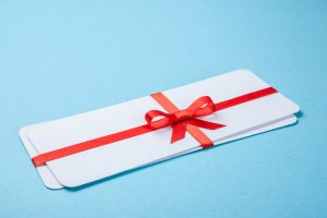 Air tickets as a gift with a red ribbon and bow.